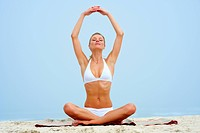 Portrait of a happy young woman practicing yoga by raising her hands at the beach