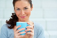 Closeup portrait of happy young woman holding a coffee cup