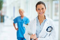 Happy young female medical doctor with stethoscope and clipboard