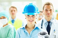 Beautiful confident young female architect in blue helmet smiling with people standing behind