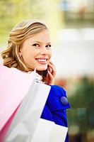 Portrait of a cute young woman holding shopping bags and speaking an a mobile