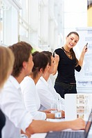 Business people looking at their leader while she´s explaining something on whiteboard during seminar
