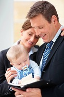 Portrait of smiling business couple with their cute baby