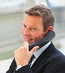 Closeup portrait of happy young business man speaking on the phone