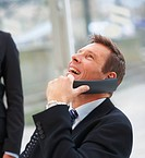 Portrait of happy young business man laughing on a conversation on the phone