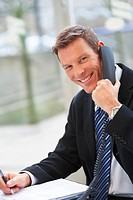 Portrait of smiling young business man speaking on the phone