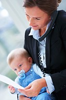 Closeup portrait of happy young business woman holding a baby and speaking on the phone