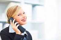 Closeup portrait of a smiling businesswoman holding a telephone receiver
