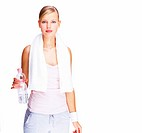 Portrait of cute young woman with water bottle in hand and towel around her neck standing on white background