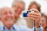 Closeup of senior man hands holding a camera for self photograph with three old ladies behind in blur background