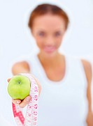 Closeup of Woman hand showing measurement tape and fresh green apple as healthy diet