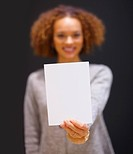 Young African American woman holding blank white piece of paper isolated with dark background