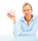 Young unhappy woman holding piggybank over white background