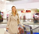 Portrait of a smiling young woman with shopping bag near an escalator standing at a mall