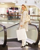 Portrait of a smiling young woman with shopping bag near an escalator