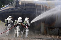 "Keeping a steady stream of water, firefighters battle a live fire while participating in an aircraft ""crash"" drill July 21, 2010, at the Combat Readin..."