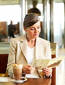 Portrait of a mature woman reading menu card in cafe