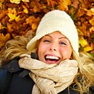 Closeup portrait of a beautiful woman lying on ground covered with leaves and smiling