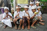 Ubud (Bali, Indonesia): children in traditional dress, enjoying an ice-cream after a ceremony in a Hindu temple