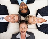 Happy team of business colleagues lying in a circle