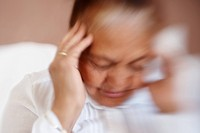 Blurred image of an old woman suffering from headache