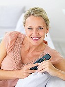 Portrait of an elderly woman relaxing at home , holding the television remote controller