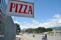 Dili (East Timor): a pizza's board along the main road to the airport