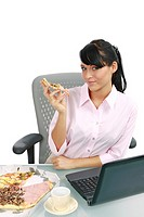 Young business woman in the office with a notebook have a break, eating pizza