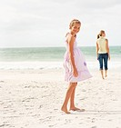 Cute teenage girl at the beach with her mother on a stroll at the background
