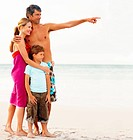 Portrait of a family smiling while at the sea shore, father pointing away
