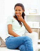Portrait of a smiling African American young woman sitting on couch at home