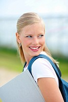 Happy young female student carrying her bag and a folder while outdoors