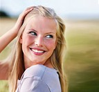 Pretty young blond female smiling, playing with her hair