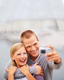 Happy young couple holding a camera in front, self photography