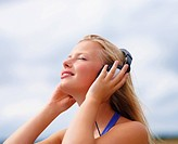 Happy young woman listening to music outdoors