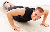 Portrait of a smart young man smiling while doing a pushup