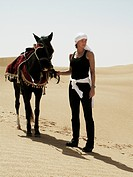 Woman with a horse in the desert, Tunisia.