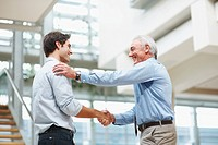 Business agreement _ Senior and young male executives shaking hands at office