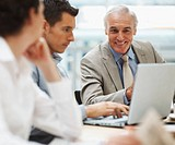 Happy senior business man with colleagues in a meeting _everyone looking at laptop