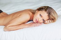 Attractive naked young woman lying on bed