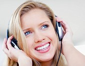 Closeup portrait of a smiling young woman listening to music over the headphones