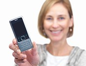 Portrait of happy mature businesswoman displaying a cellphone isolated over white background