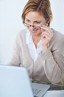 Portrait of mature business woman working at her desk with a laptop