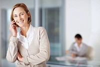Portrait of middle aged businesswoman talking on mobile with a colleague working in background