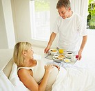 Loving happy middle aged man serving breakfast to his pregnant wife on bed