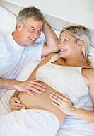 Happy mature couple lying in bed with man fondling his wife´s pregnant belly