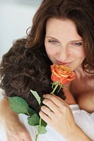 Closeup portrait of a pretty woman smelling a flower while being caressed by husband