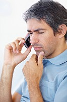 Portrait of a mature man looking worried while talking on mobile phone