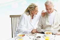 Happy mature woman with her husband reading newspaper at breakfast table