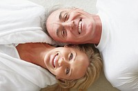 Top view closeup of a smiling mature couple lying on the floor